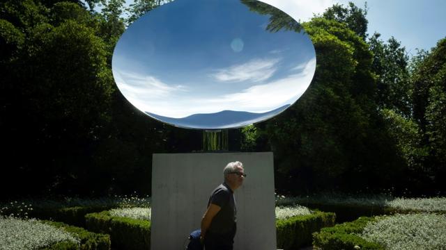 """Le sculpteur britannique Anish Kapoor devant son oeuvre """"Sky Mirror"""" lors de la présentation de l'exposition """"Anish Kapoor: œuvres, pensées, expériences"""", le 6 juillet 2018 dans le parc de la Fondation Serralves, à Port, au Portugal [MIGUEL RIOPA / AFP]"""