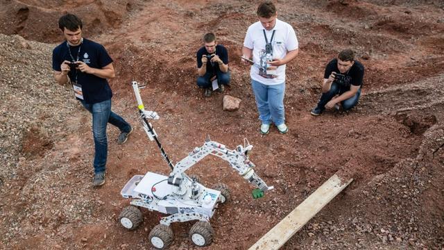"""Des membres de l'équipe de l'Université de Kielce et leur prototype de robot martien, """"Impuls"""", lors du concours européen des robots explorateurs à Checiny, en Pologne, le 5 septembre 2015 [WOJTEK RADWANSKI / AFP]"""