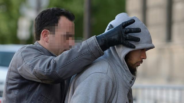 Alexandre Dhaussy, qui a poignardé un militaire à la Défense, escorté par un policier le 29 mai 2013 à Paris [Eric Feferberg / AFP/Archives]