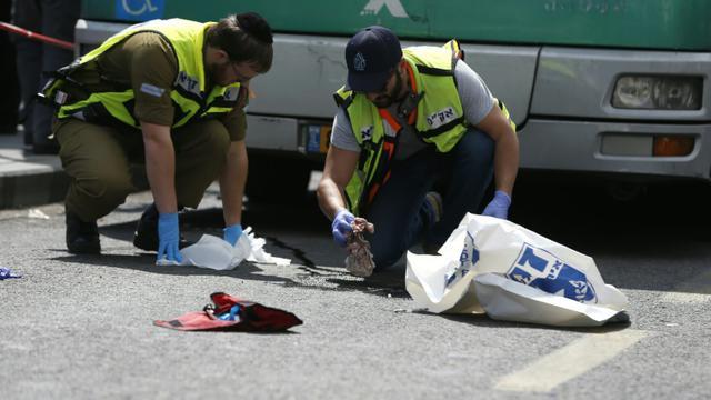 Des enquêteurs israéliens examinent les lieux après l'attaque perpétrée contre un Israélien à Jérusalem, le 8 octobre 2015 [AHMAD GHARABLI / AFP]