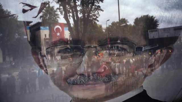 Photo prise à travers une banderole électorale tranparente affichant un portrait du Premier ministre turc Ahmet Davutoglu le 29 octobre 2015 à Istanbul [DIMITAR DILKOFF / AFP]