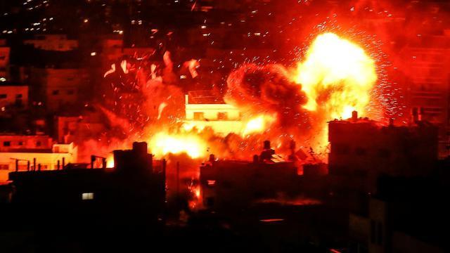 Une boule de feu s'élève au-dessus du site d'un bâtiment du mouvement islamiste palestinien Hamas, visé par des tirs israéliens, le 12 novembre 2018 dans la bande de Gaza [MAHMUD HAMS / AFP]