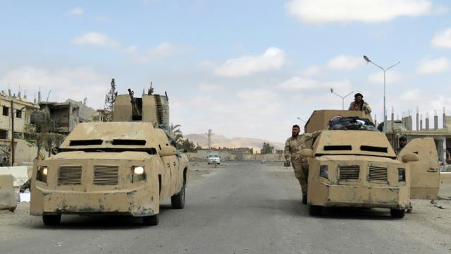 Des membres des forces syriennes dans des blindés à Palmyre, le 27 mars 2016  [STRINGER / AFP]