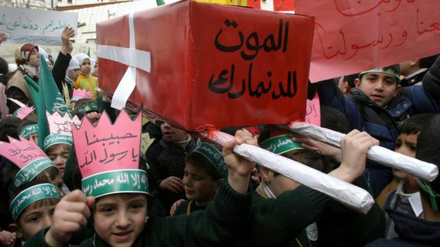 """De jeunes Palestiniens défilent à Hébron, en Cisjordanie, le 13 février 2006 avec un faux cercueil ceint d'un drapeau danois sur lequel est inscrit """"Mort au Danemark"""" [HAZEM BADER / AFP/Archives]"""