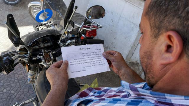 """Un Syrien lit un tract portant le sceau des forces gouvernementales et appelant la population à """"rejoindre le (processus de) réconciliation"""" à Binnish, dans le nord-ouest de la Syrie, le 9 août 2018 [OMAR HAJ KADOUR / AFP]"""