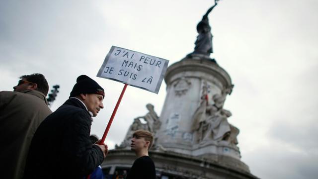 Un homme porte une pancarte à l'occasion du rassemblement en hommage aux victimes des attentats, le 10 janvier 2016 à Paris [THOMAS SAMSON / AFP]