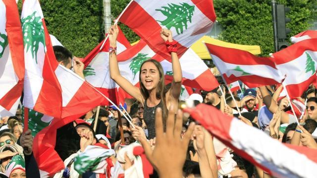 Des manifestants brandissent des drapeaux libanais lors d'un rassemblement contre le pouvoir, à Saïda, dans le sud du Liban, le 19 octobre 2019 [Mahmoud ZAYYAT / AFP]