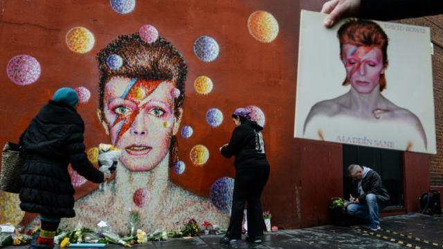 Des fans déposent des fleurs en hommage au chanteur David Bowie, après l'annonce de son décès, devant une fresque à son effigie, de l'artiste de rue australien James Cochran, dans le quartier de Brixton, à Londres, le 11 janvier 2016. [Chris RATCLIFFE / AFP]