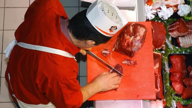 Un boucher découpe une piéce de boeuf au rayon boucherie d'un Intermarché, de Chalonnes-sur-Loire, en décembre 2004 [Frank Perry / AFP/Archives]