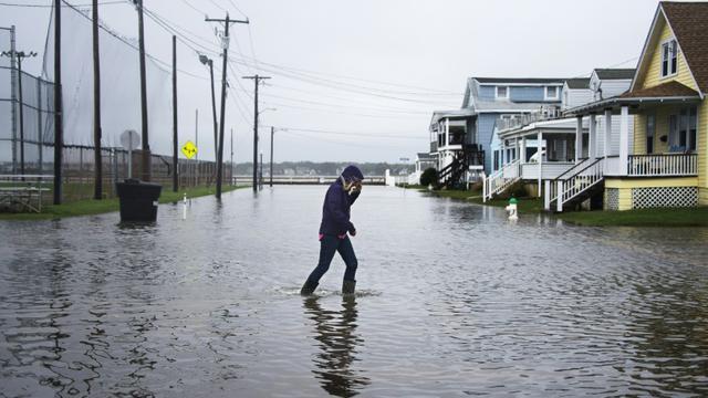 Une femme traverse une rue inondée à Ocean City, dans le Maryland, le 3 octobre 2015 [JIM WATSON / AFP]