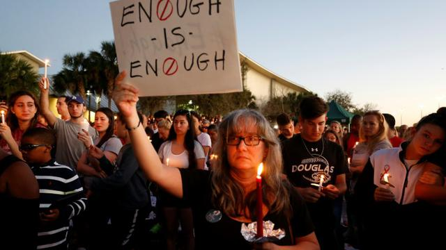 """Une manifestante brandit une pancarte clamant """"Assez c'est assez !"""" lors d'une veillée pour les victimes de la fusillade du lycée à Parkland qui a coûté la vie à 17 personnes  [RHONA WISE / AFP]"""