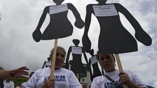 """Des proches de """"disparus"""" tiennent des pancartes sur lesquels figurent leurs noms, en octobre 2012 à Medellin [Raul Arboleda / AFP/Archives]"""