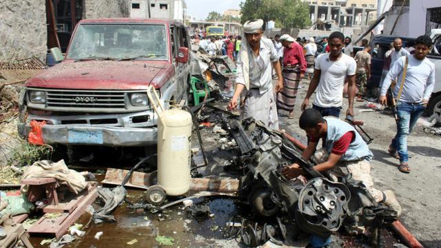 Le 13 mars 2018 à Aden au Yémen, des yéménites inspectent l'épave d'une voiture détruite par l'attentat suicide [SALEH AL-OBEIDI / AFP]