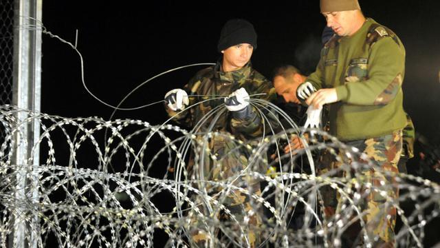 Soldats et policiers hongrois achèvent de mettre les derniers barbelés pour fermer la frontière entre la Hongrie et la Croatie à Botovo, le 16 octobre 2015 [STR / AFP]