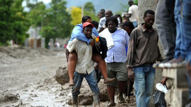 Des Haïtiens dans la boue après le passage de la tempête tropivale le 29 août 2015 à Montrouis [HECTOR RETAMAL / AFP]