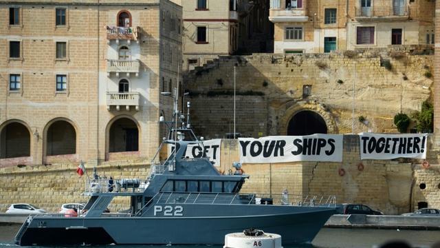 """Un bateau des gardes-côtes maltais patrouillent dans la baie de Birgu à Malte, devant des banderoles où l'on peut lire """"Get your ships together"""", le 23 septembre 2019 [Matthew Mirabelli / AFP]"""