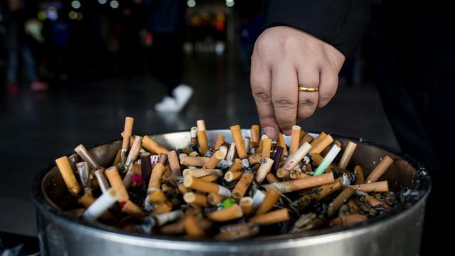 Un homme écrase une cigarette dans un cendrier dans une gare à Shanghai, le 28 février 2017 en Chine [Johannes EISELE / AFP/Archives]