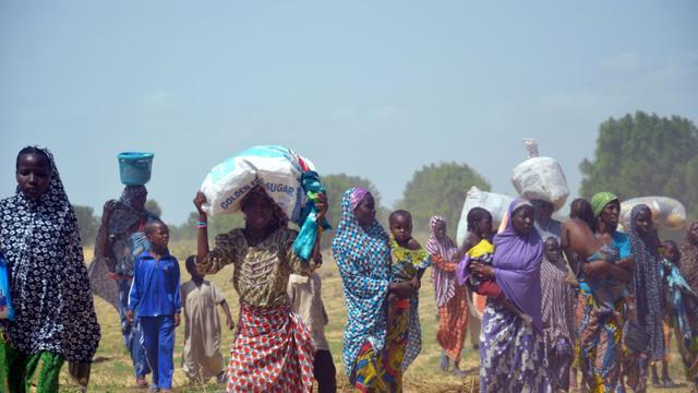 Des femmes et des enfants fuient leurs maisons incendiées par des islamistes de Boko Haram, le 3 juillet 2015 à Zabarmari, près de Maiduguri, au nord-est du Nigeria [ / AFP/Archives]