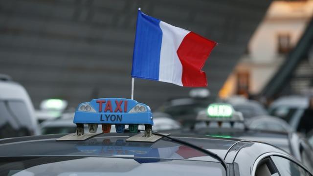 Un drapeau tricolore sur un taxi dont le chauffeur manifeste le 26 janvier 2016 à Paris [THOMAS SAMSON / AFP]