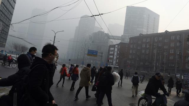 Des gens traversent une rue à Pékin un jour de pollution le 14 décembre 2015 [GREG BAKER / AFP/Archives]