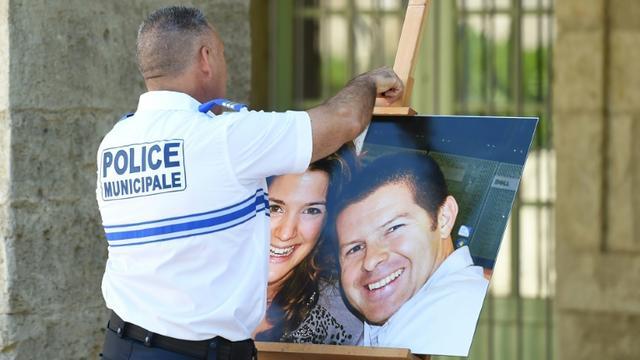Un officier de police tient le 20 juin 2016 à Pézénas dans l'Hérault une photographie de Jessica Schneider et Jean-Baptiste Salvaing, victimes d'un assassinat jihadiste à Magnanville, le 13 juin 2016 [SYLVAIN THOMAS / AFP/Archives]