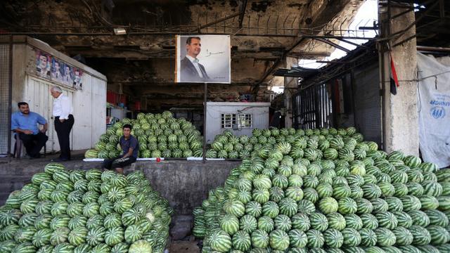 Des négociants syriens près du portrait du président Bachar al-Assad au marché des Halles de Damas, le 21 septembre 2015 [JOSEPH EID / AFP]
