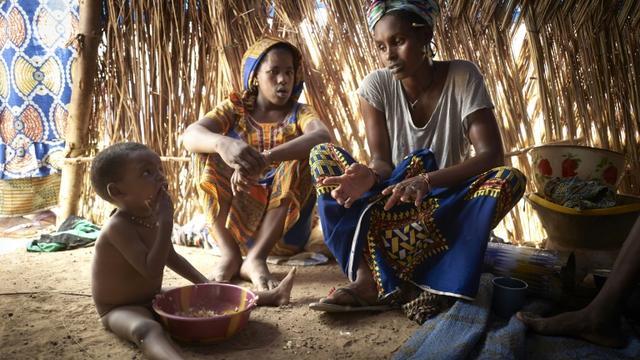 Une mère et ses enfants, de la communauté peule, sous une tente d'un camp de réfugiés installé dans la banlieue de Bamako, le 8 mai 2019  [MICHELE CATTANI / AFP]
