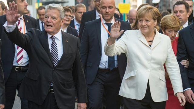 La Chancelière allemande Angela Merkel et le président Joachim Gauck saluent la foule, le 3 octobre 2015 à Francfort, à l'occasion des 25 ans de la Réunification de l'Allemagne [BORIS ROESSLER / POOL/AFP]