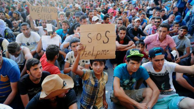 Des centaines de migrants assis devant la gare de Budapest, le 2 septembre 2015 en Hongrie [ATTILA KISBENEDEK / AFP]