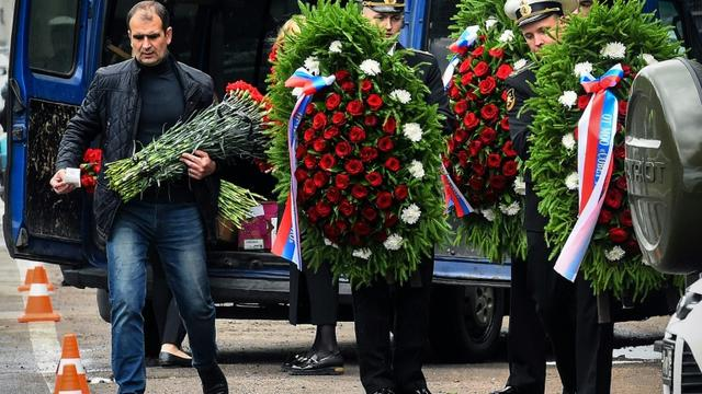 Des militaires de la Marine russe transportent des couronnes mortuaires avant les funérailles des 14 officiers tués dans l'incendie d'un petit sous-marin nucléaire, le 6 juillet 2019 à Pétersbourg [OLGA MALTSEVA / AFP]