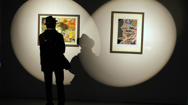 Un homme regarde des dessins d'auteurs américains de comics lors du festival de BD d'Angoulême le 26 janvier 2012 [PIERRE ANDRIEU / AFP/Archives]
