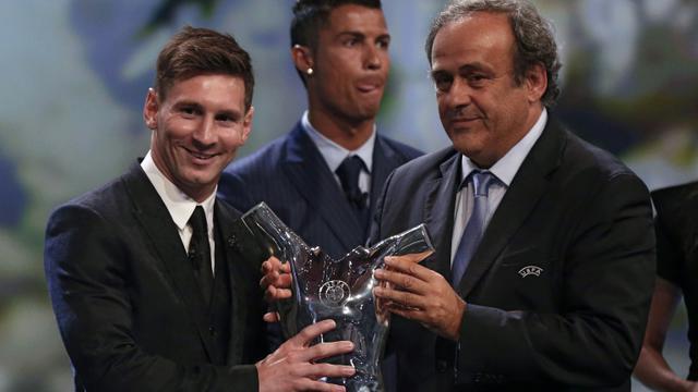 Lionel Messi reçoit des mains de Michel Platini, président de l'UEFA, le trophée de meilleur joueur UEFA de l'année devant Cristiano Ronaldo à la fin du tirage au sort de Ligue des Champions à Monaco le 27 août 2015 [VALERY HACHE / AFP]