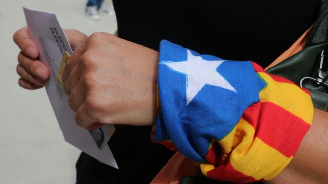 Une femme, un foulard indépendantiste au poignet, dans un bureau de vote de Badalona en Espagne, le 27 septembre 2015  [Cesar Manso / AFP]