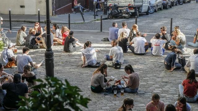 Assis sur les pavés parisiens pour boire un verre, le 29 mai 2020 [GEOFFROY VAN DER HASSELT / AFP]