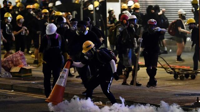 Un manifestant pro-démocratie couvre une grenade lacrymogène avec un cône de signalisation, le 28 juillet 2019 à Hong Kong [Anthony WALLACE / AFP/Archives]