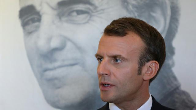 Emmanuel Macron devant le portrait de Charles Aznavour à Erevan lors du sommet de la francophonie, le 11 octobre 2018 [ludovic MARIN / AFP]