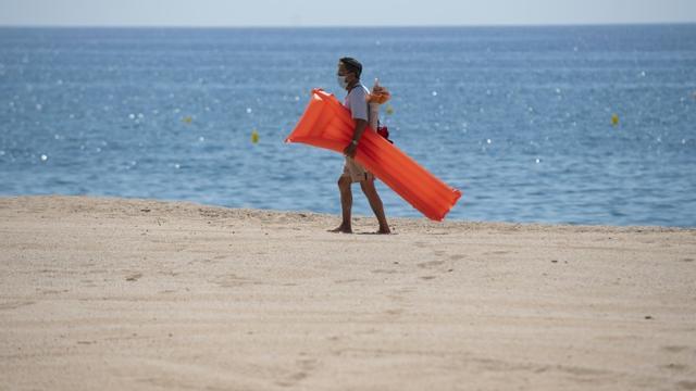 Un vacancier porte un masque de protection sur la plage de Lloret de Mar, le 22 juin 2020 en Espagne [Josep LAGO / AFP/Archives]