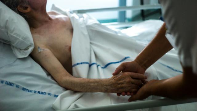 Une infirmière tient la main d'un patient dans une unité de soins palliatifs d'Argenteuil, le 22 juillet 2013 [FRED DUFOUR / AFP/Archives]