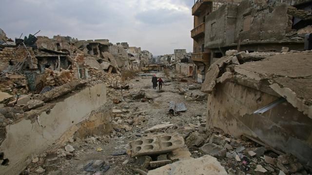 Des Syriens traversent une rue détruite du quartier al-Akroub d'Alep, le 17 décembre 2016 [Youssef KARWASHAN / AFP]