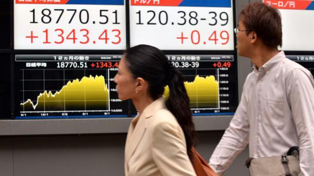 Des passants regardent un tableau d'indices boursiers, le 9 septembre 2015 à Tokyo [YOSHIKAZU TSUNO / AFP]