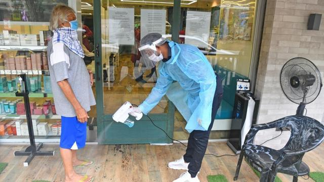 Un employé désinfecte les pieds d'un client avant qu'il entre dans un salon de coiffure, le 28 juin 2020 à Bombay, en Inde [INDRANIL MUKHERJEE / AFP]