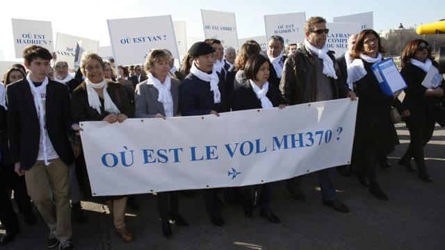 Ghyslain Wattrelos (3e à d), proche de victimes du vol MH370 de la Malaysia Airlines qui a disparu en mars 2014, en tête d'une marche silencieuse vers le Palais de l'Elysée à Paris, le 8 mars 2015 [THOMAS SAMSON / AFP/Archives]