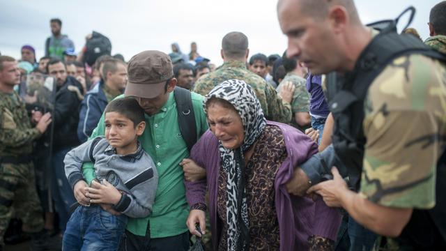 Sous la pluie, des migrants épuisés, le 10 septembre 2015, à Gevgelija, en Macédoine tentent de monter dans un bus pour se mettre à l'abri [ROBERT ATANASOVSKI / AFP]