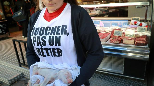Une militante vegan devant une boucherie à Paris le 22 septembre 2018 [JACQUES DEMARTHON / AFP]