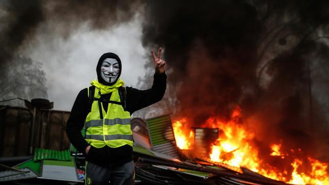 Un manifestant portant un gilet jaune et un masque près d'une barricade en feu, à Paris le 1er décembre 2018 [Abdulmonam EASSA / AFP]