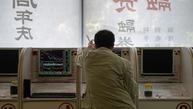 Les cours des actions sont affichés dans une société de placement à Pékin, le 11 octobre 2018 [Nicolas ASFOURI / AFP]
