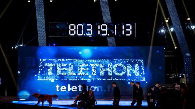 Des invités marchent devant le compteur de dons de l'édition 2016 du Téléthon, à Paris, le 4 décembre [PHILIPPE LOPEZ / AFP/Archives]