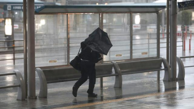Un homme s'abrite des fortes précipitations causées par le typhon Trami à Kagoshima (sud-ouest du Japon) le 30 septembre 2018. [Behrouz MEHRI / AFP]