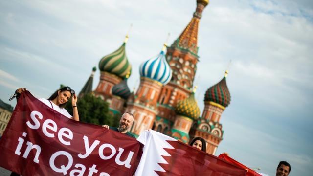 """Des personnes déploient une banderole """"à bientôt Qatar"""" sur la Place Rouge de Moscou, à la veille de la finale du Mondial-2018 en Russie, le 14 juillet 2018 [Jewel SAMAD / AFP/Archives]"""