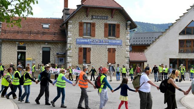 Environ 300 personnes ont formé une chaîne humaine le 5 mai 2018 dans le village d'Autrans (Isère) pour protester contre les compteurs communicants Linky [JEAN-PIERRE CLATOT / AFP]